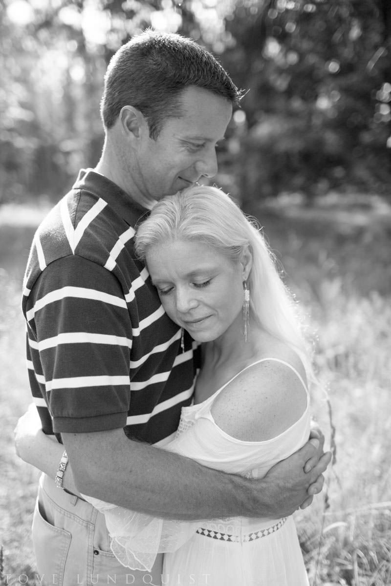 Stående svartvitt porträttbild på man som kärleksfullt omfamnar en kvinna. Beloved - Moment Design - parfotografering i Hycklinge Hage. Fotograf är Tove Lundquist, verksam bröllopsfotograf och porträttfotograf i Oskarshamn, Småland.