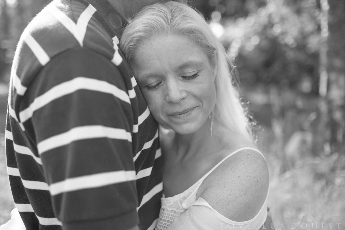 Svartvitt porträttbild på kvinna som blundar när hon kärleksfullt blir omfamnad av sin man. Beloved - Moment Design - parfotografering i Hycklinge Hage tillsammans med kärleksfullt par. Fotograf är Tove Lundquist, verksam bröllopsfotograf Oskarshamn, Småland.