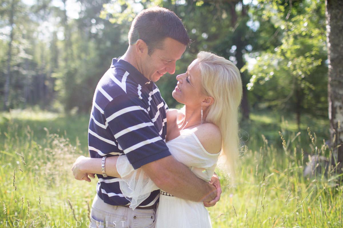 Somrig färgbild på kärleksfullt par. Porträttfotograferingen skedde i Hycklinge Hage, Oskarshamn. Fotograf är Tove Lundquist.