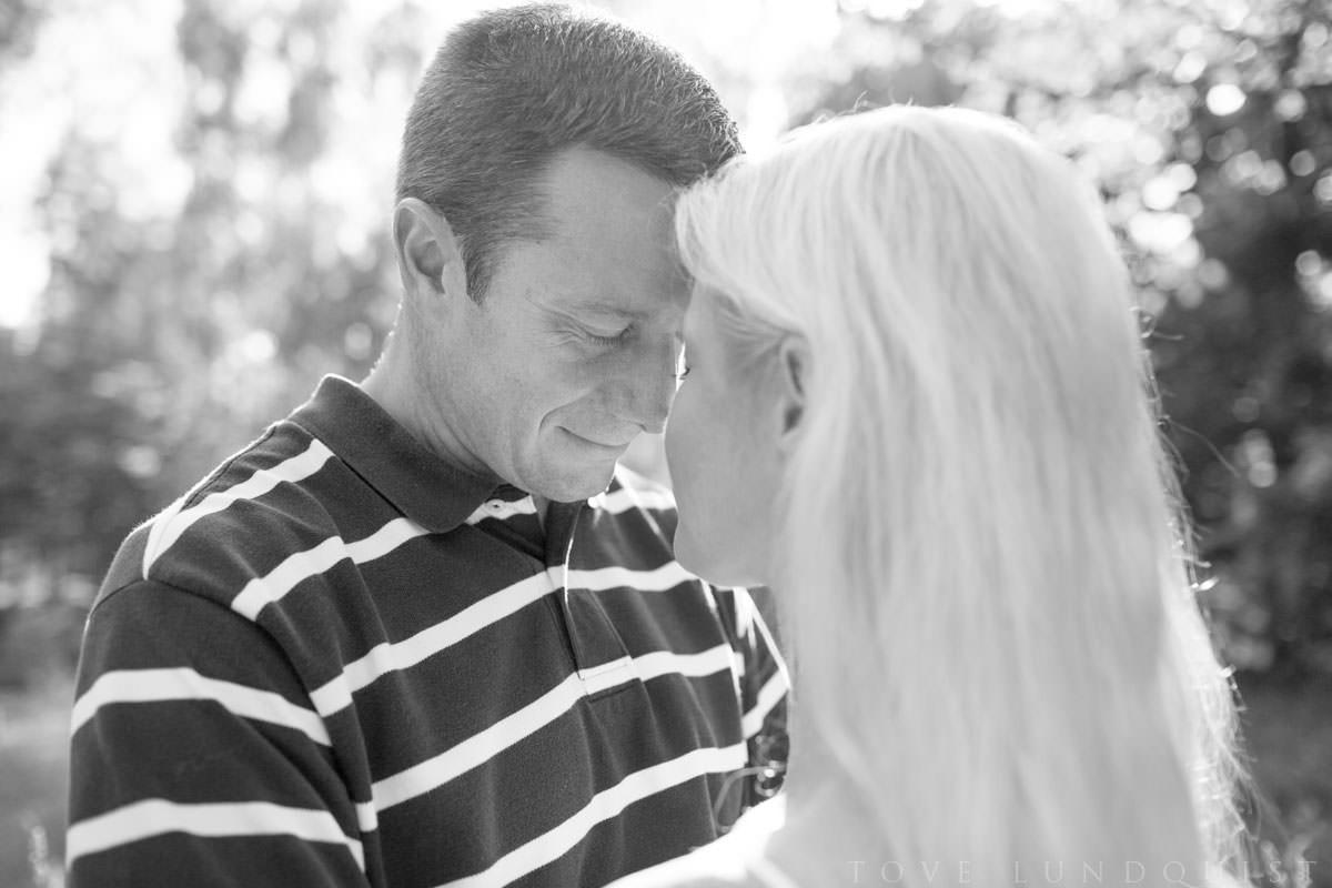 Svartvit porträttbild på man som blundar när han kärleksfullt lutar sin panna mot en kvinna. Kärleksfotografering beloved - Moment Design - i Hycklinge Hage, fotograf är Tove Lundquist - verksam fotograf inom bröllop och porträtt i Oskarshamn, Småland.