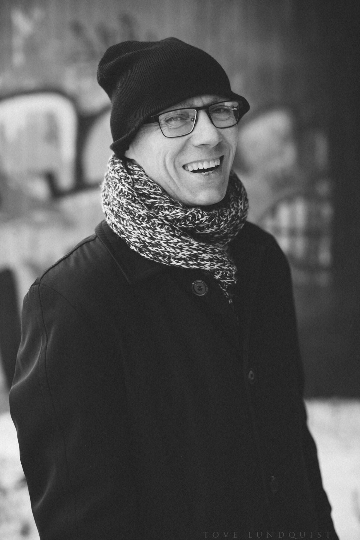 Svartvitt enskilt porträtt på man framför graffitivägg, Malmö. Foto: Tove Lundquist.