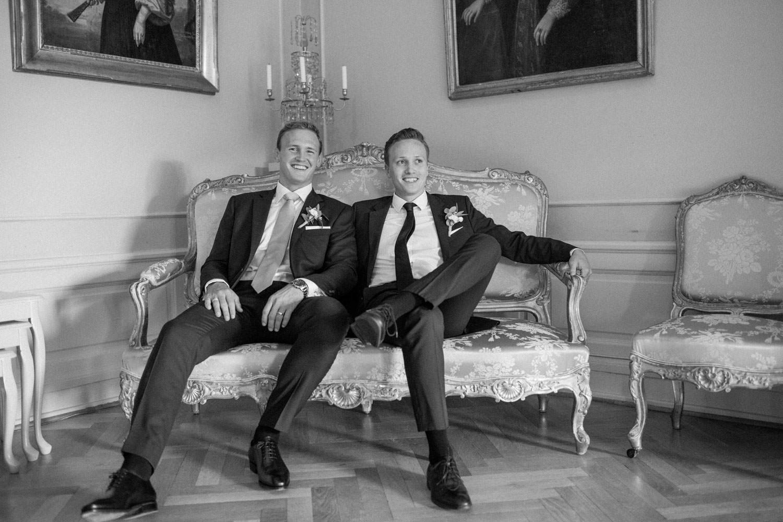 Två bröder sitter i en soffa inomhus under ett bröllop på Trolleholms slott i Skåne.