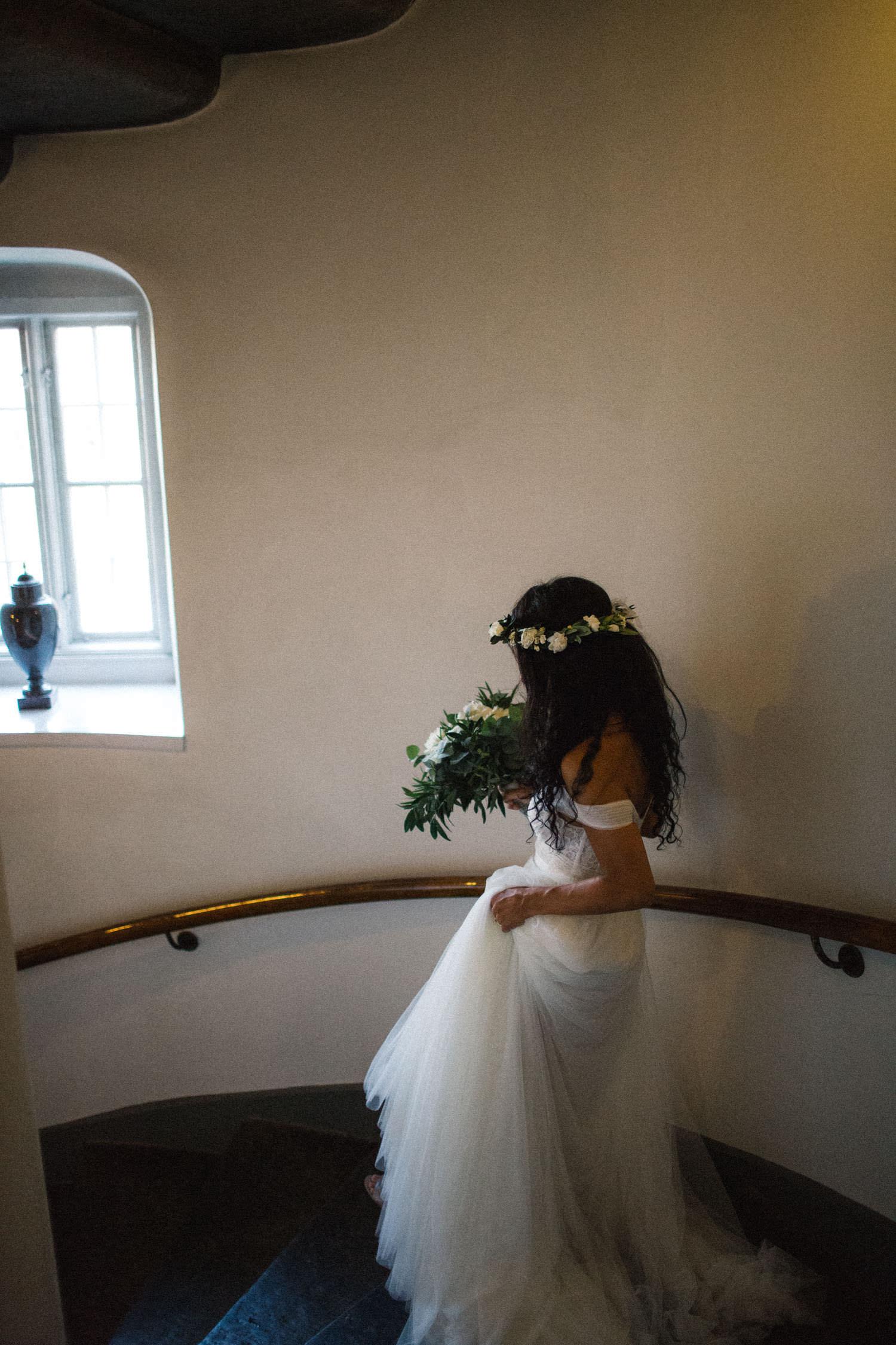 Bruden Ashley Ljungbäck går nedför trappan på Trolleholms slott. Brudklänning från Mia Grace Bridal, florist är Lilla Hults blommor. Fotograf Tove Lundquist i Skåne.