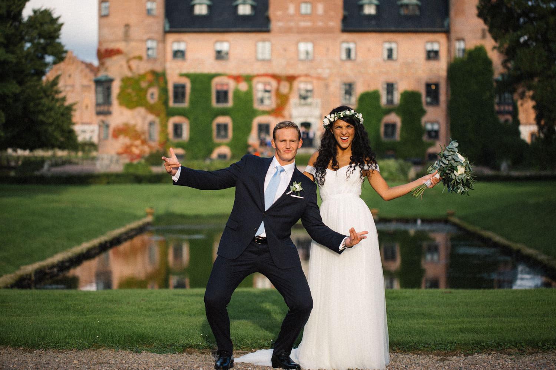 Brudpar Ashley och Christoffer Ljungbäck står framför Trolleholms slott i Skåne. Florist är Lilla Hult Blommor.