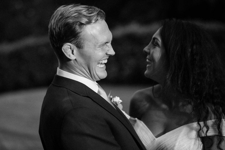 Svartvitt porträtt på ett skrattande brudpar under bröllop på Trolleholms Slott i Skåne.