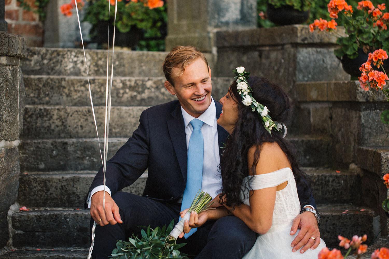 Brudparet Christoffer och Ashley Ljungbäck sitter på trappan vid Trolleholms Slott. Foto av Tove Lundquist, bröllopsfotograf Skåne.