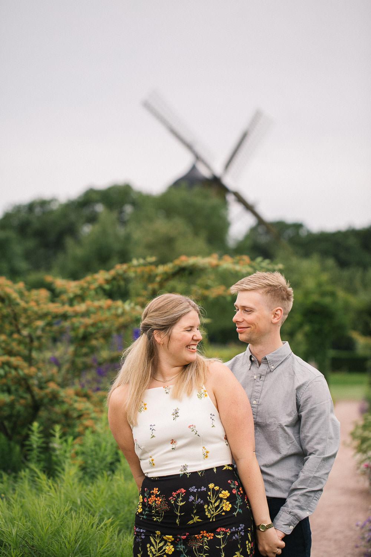 Foto i färg på förälskat par som skall gifta sig. I bakgrunden syns Slottsmöllan. Foto: Tove Lundquist, bröllopsfotograf i Malmö.