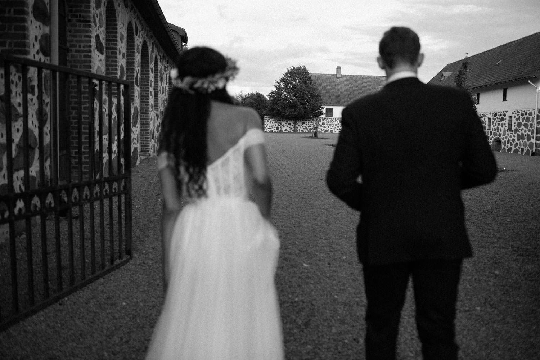 Svartvitt foto på gående brudpar på Trolleholms slott.