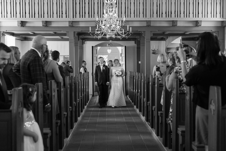 Brudparets ingång under en vigsel i Östra Torps kyrka, Smygehamn. Foto: Tove Lundquist, bröllopsfotograf Smygehamn.