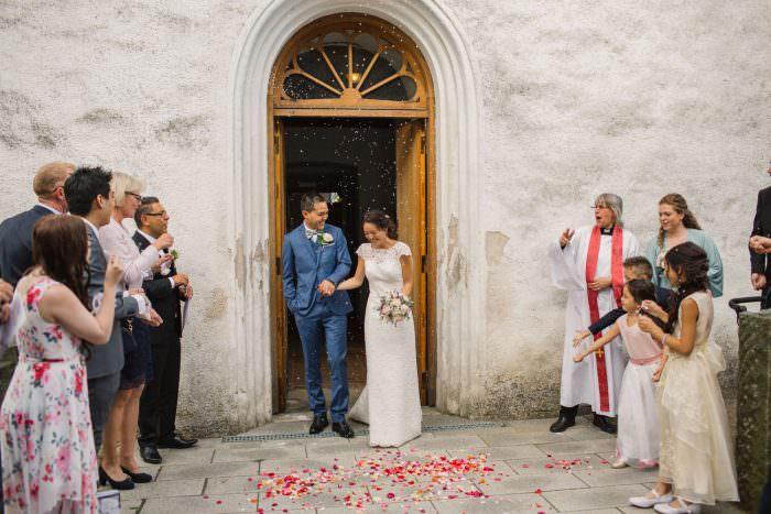 Brudpar med gäster utanför Borgeby kyrka i Bjärred, Skåne. Foto: Tove Lundquist, bröllopsfotograf i Skåne. Brudklänning från Skräddarhuset Malmö.