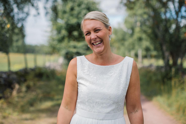 Porträtt på glad brud på Lövö. Brudklänning från Sofia Moore, smycken från Lily and Rose.