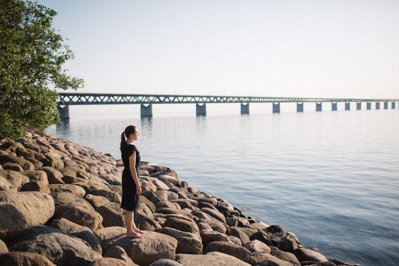 Fotografi i färg på kvinna som tittar ut över havet vid Utsiktspunkt Öresundsbron. Fotografen är Tove Lundquist, Skåne.