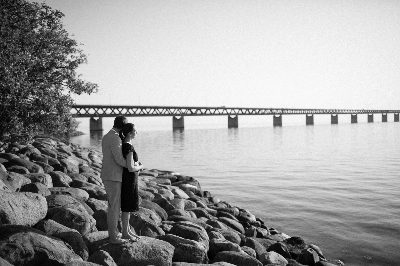 Svartvitt foto på brudpar som tittar ut över havet vid Utsiktspunkt Öresundsbron. Fotografen är Tove Lundquist, Malmö.