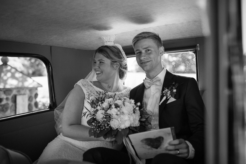 Svartvit bild på brudpar i bil efter vigseln. Foto: Tove Lundquist, bröllopsfotograf Smygehamn.