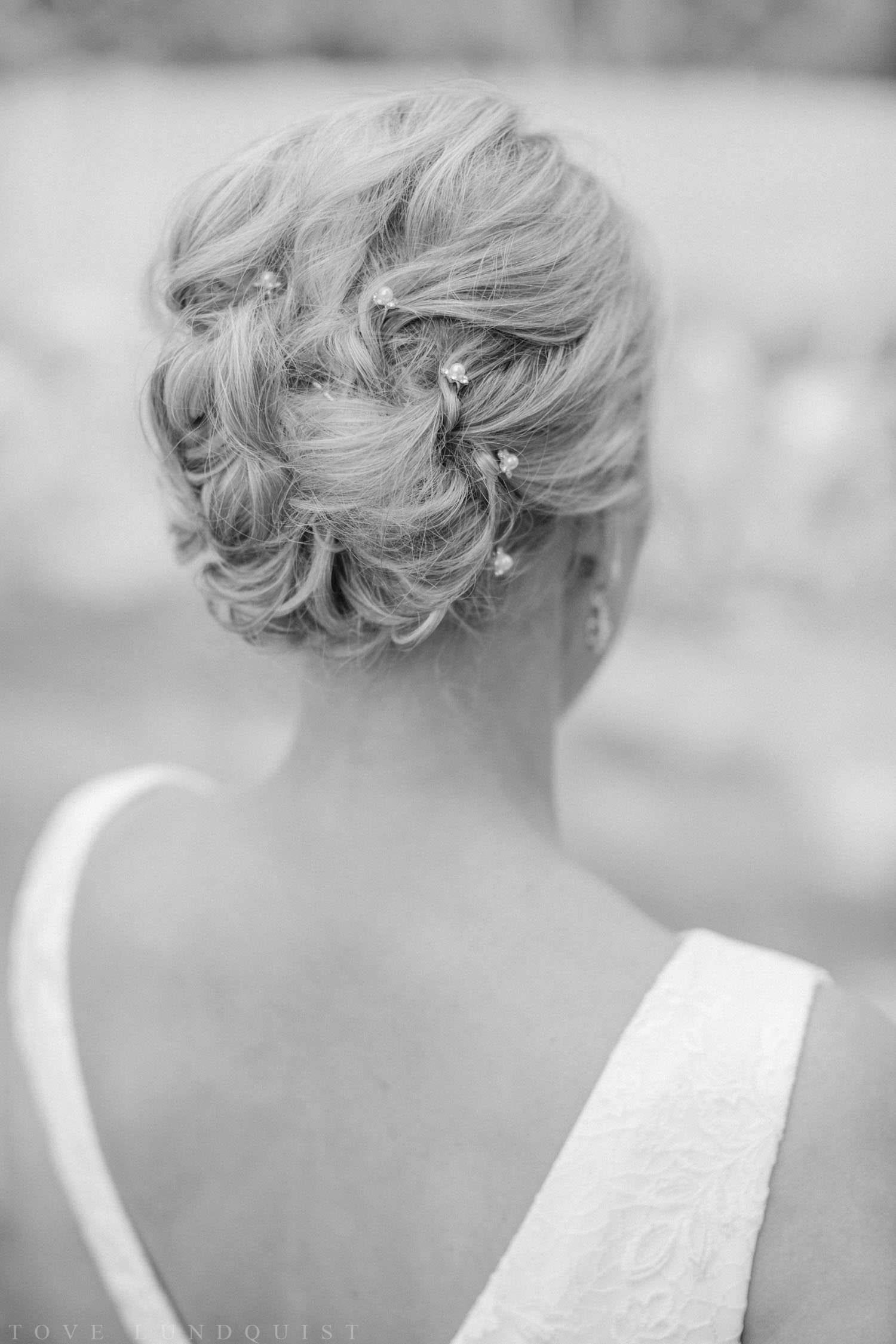 Svartvitt fotografi på brud iklädd bröllopsklänning från Sofia Moore. Frisyr av Studio 1, Mönsterås.