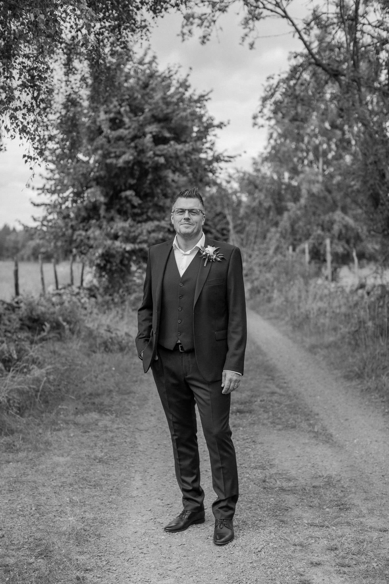 Svartvitt porträtt på brudgum. Platsen är Lövö, bröllopet skedde i Mönsterås. Kostymen kommer från Dressmann.