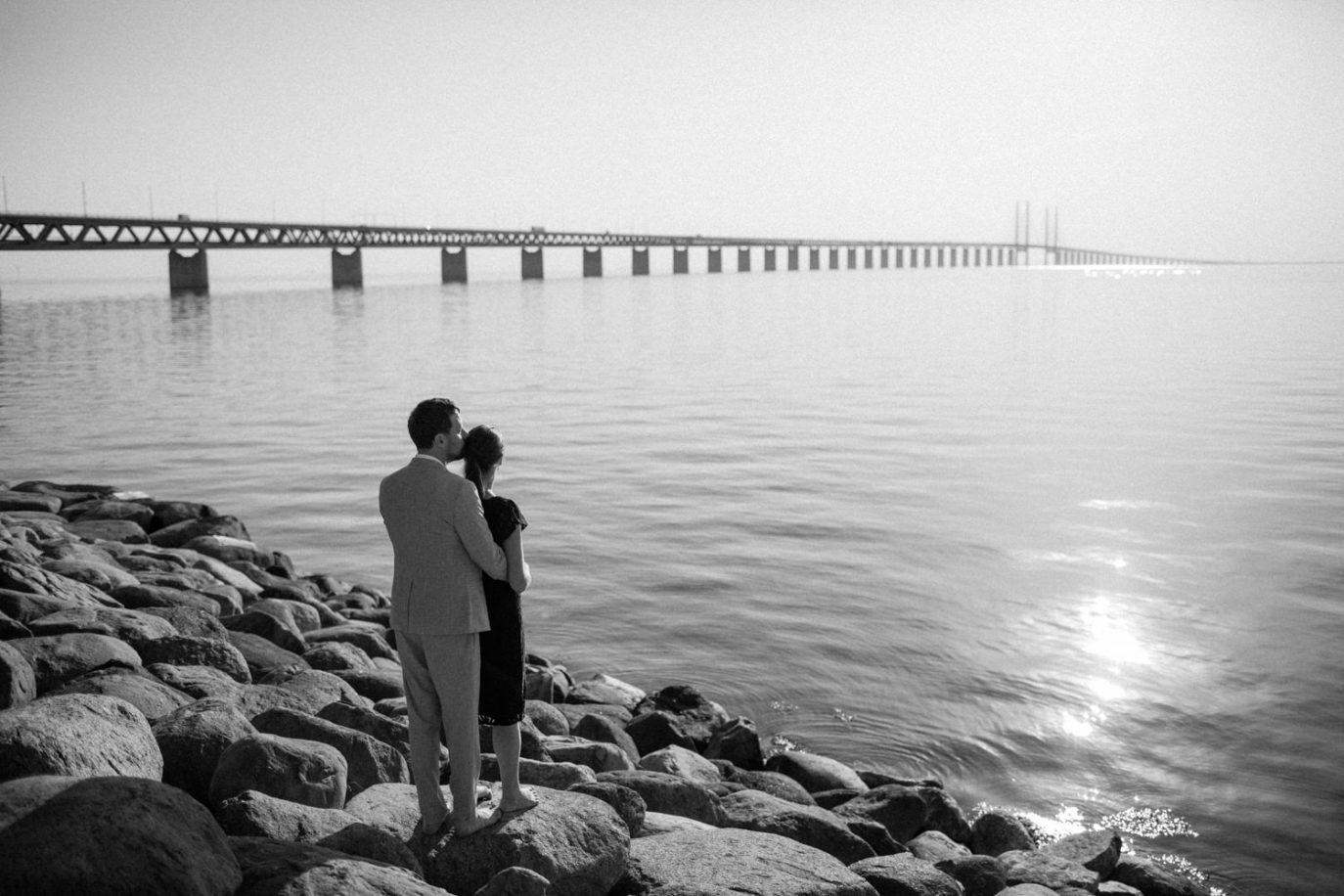 Svartvitt foto på brudpar som tittar ut över havet vid Utsiktspunkt Öresundsbron. Fotografen är Tove Lundquist, Skåne.