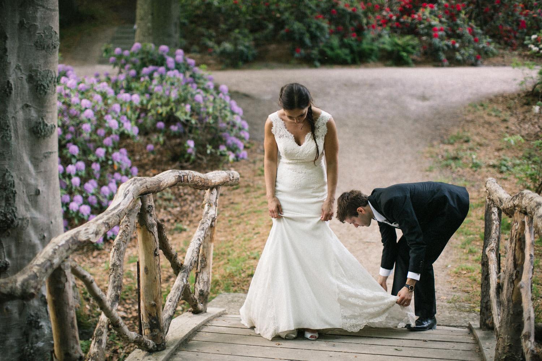 Brudgum rättar till brudklänningen under bröllopsporträtt i Sofiero Slott, bröllopsfotograf Helsingborg.