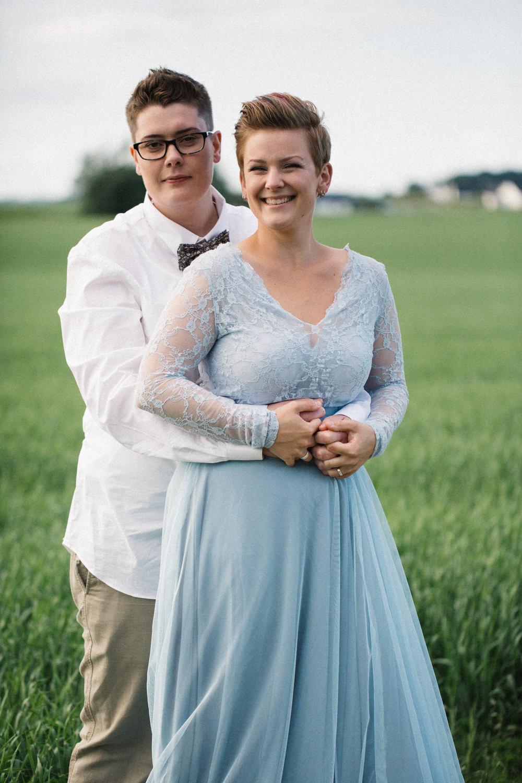 Porträtt på två brudar under en fotografering på Stallgården i Vellinge, klänning kommer från SensibleM, miljövänlig fluga kommer från Metzerverket. Foto: Tove Lundquist, bröllopsfotograf i Skåne.