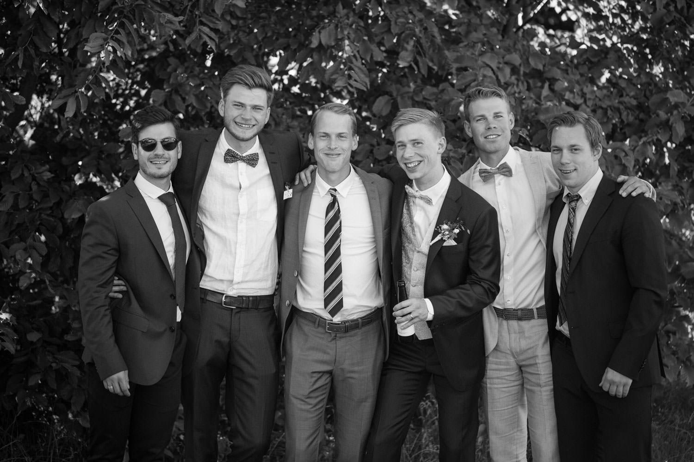 Svartvitt porträtt på brudgum med hans vänner, Smygehamn. Foto: Tove Lundquist, bröllopsfotograf Malmö.