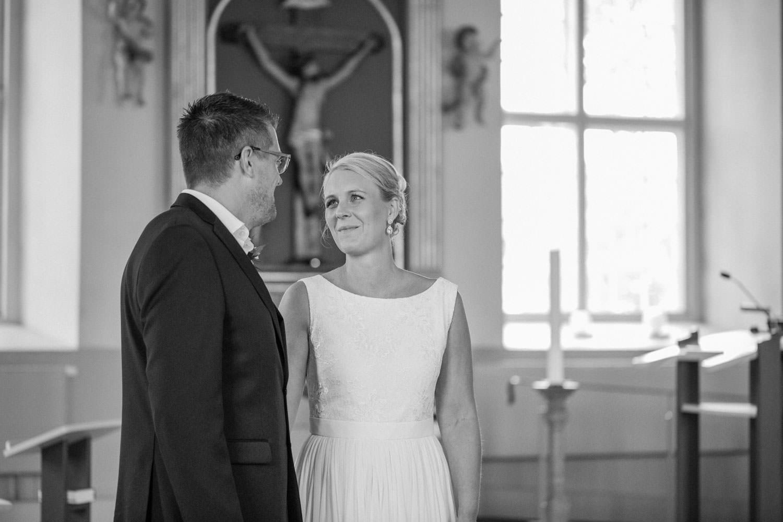 Svartvitt foto på brudpar som gifter sig i Mönsterås kyrka. Bröllopsfotograf är Tove Lundquist. Brudgummens kostym kommer från Dressmann. Brudens klänning kommer från Sofia Moore.