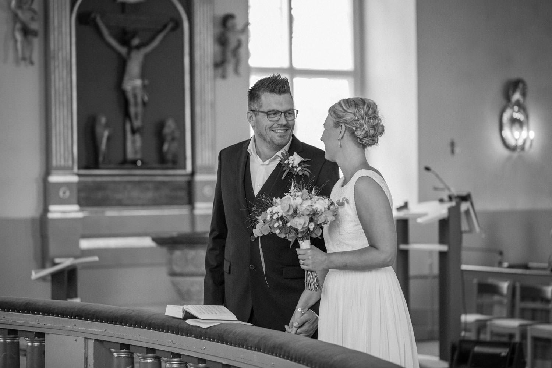 Svartvitt foto på brudpar som gifter sig i Mönsterås kyrka. Brudgummens kostym kommer från Dressmann. Brudens klänning kommer från Sofia Moore.