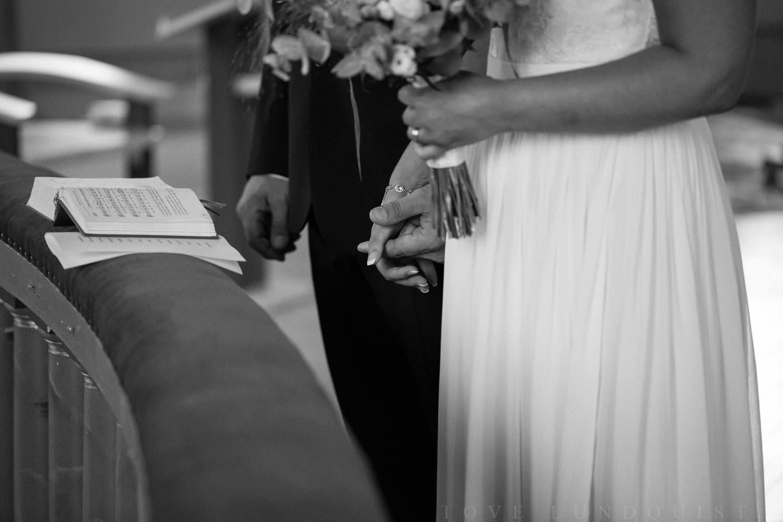 Brudpar håller varandra i händerna. Brudens klänning kommer från Sofia Moore. Brudgummens kostym kommer från Dressmann.