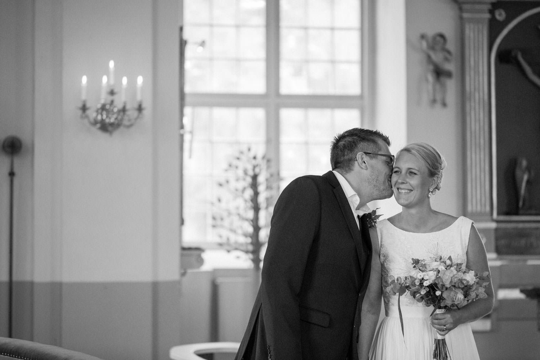 Svartvitt foto på brudgum som pussar bruden. Fotograf är Tove Lundquist. Brudgummens kostym kommer från Dressmann. Brudens klänning kommer från Sofia Moore.