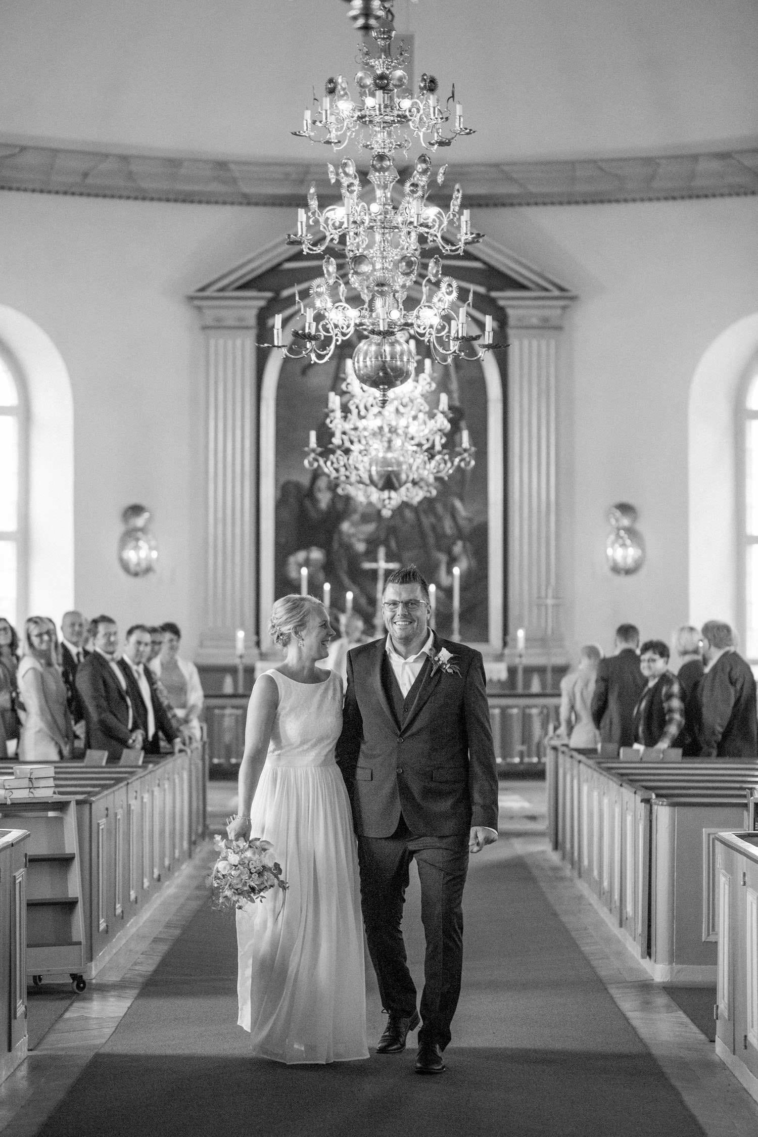 Brudpar går ut ur kyrkan efter vigsel, bröllop i Mönsterås.