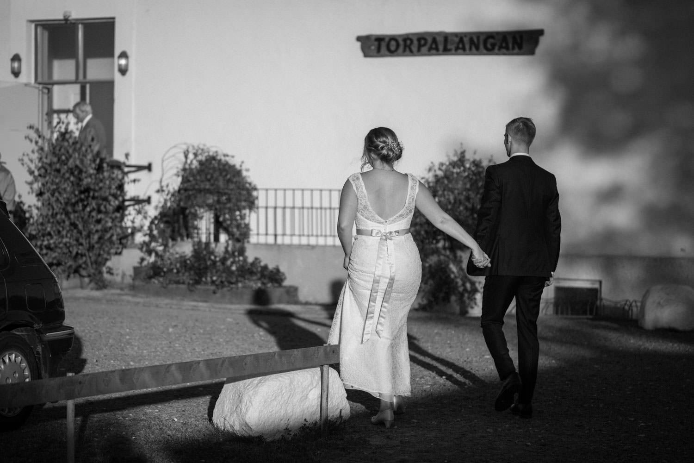 Svartvitt foto på brudpar som går. Bröllopsporträtt vid Smygehamn, Skåne. Brudklänning från Nicolai brudekjoler. Kostym från J.Lindeberg. Väst, fluga och näsduk kommer från Splendor skrädderi i Borås. Foto: Tove Lundquist, bröllopsfotograf Trelleborg.