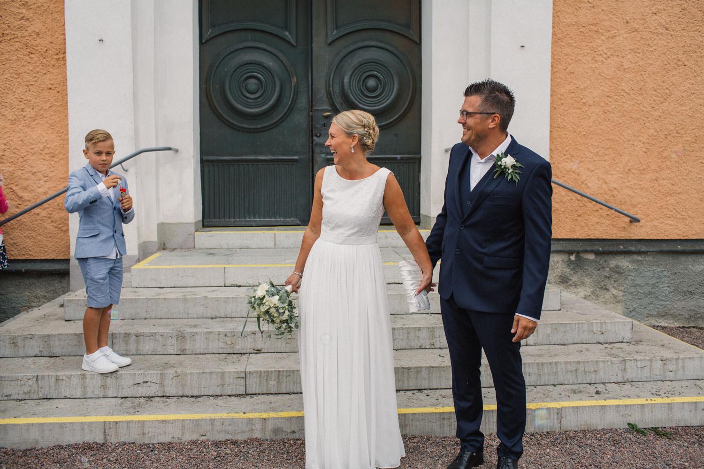 Brudpar står utanför kyrkan tillsammans med sina gäster.