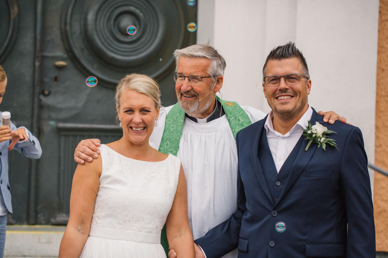 Brudpar står utanför kyrkan tillsammans med sina gäster, bröllop i Mönsterås.