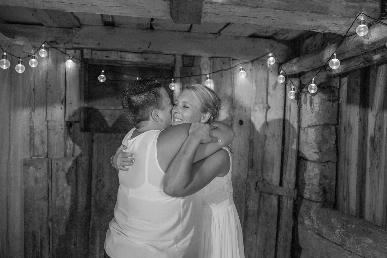 Brud och vän kramar om varandra i en Photo Booth. Plats är Kaffetorpet Oknö, Småland.