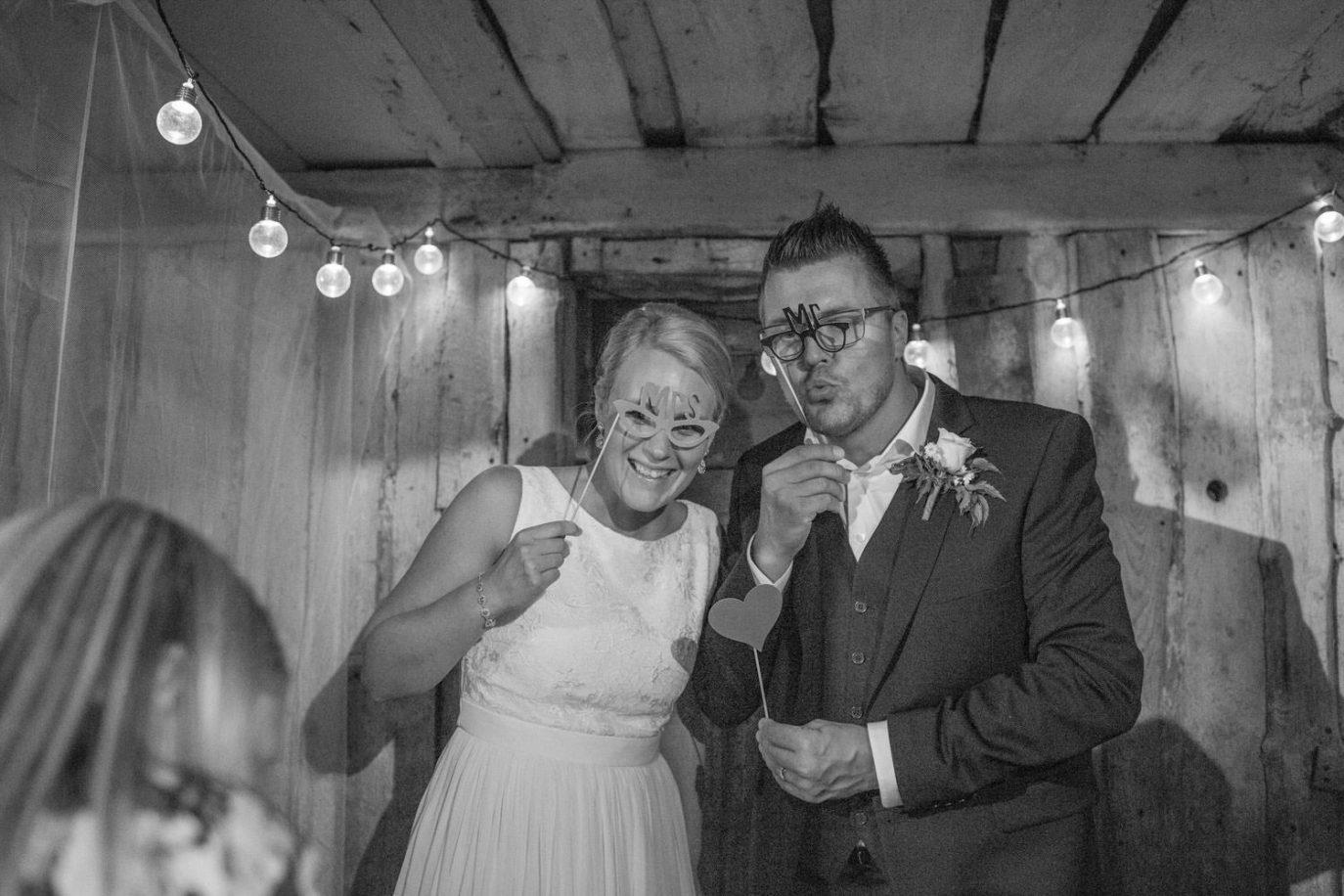 Svartvitt foto på brudpar roar sig i ett Photo Booth. Plats är Kaffetorpet Oknö, Småland.
