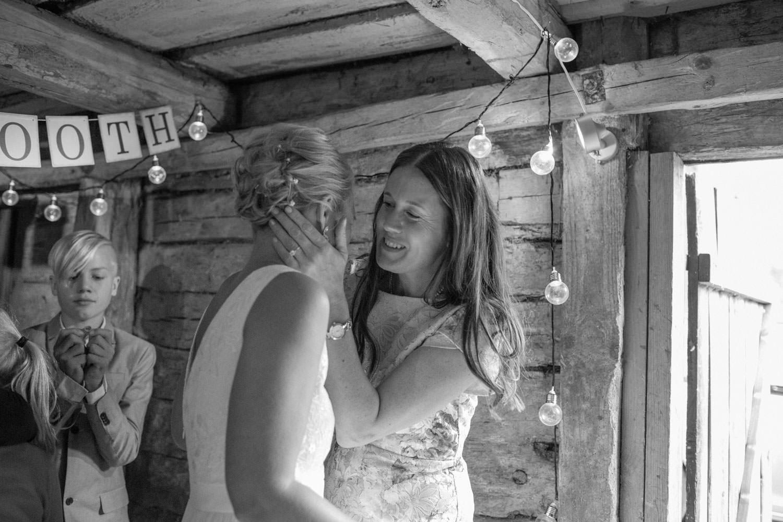 Svartvitt foto på svägerska som pussar bruden i ett Photo Booth. Plats är Kaffetorpet Oknö, Småland.