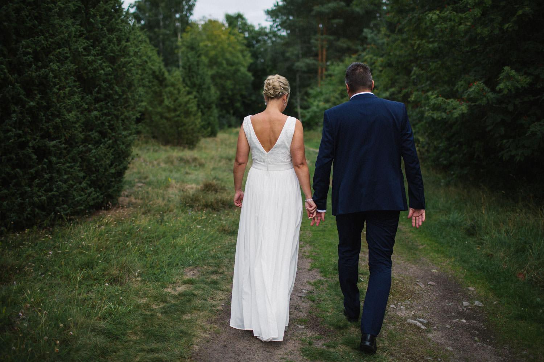 Brudpar går i skogen vid Oknö. Brudklänning från Sofia Moore, kostym från Dressmann.