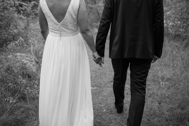 Svartvitt porträtt på brudpar som går i skogen vid Oknö. Brudklänning från Sofia Moore, kostym från Dressmann.