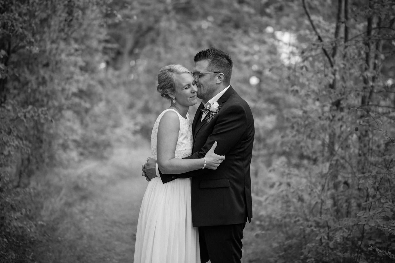 Naturligt och avslappnat svartvitt porträtt på brudpar vid Oknö. Brudklänning från Sofia Moore, kostym från Dressmann.