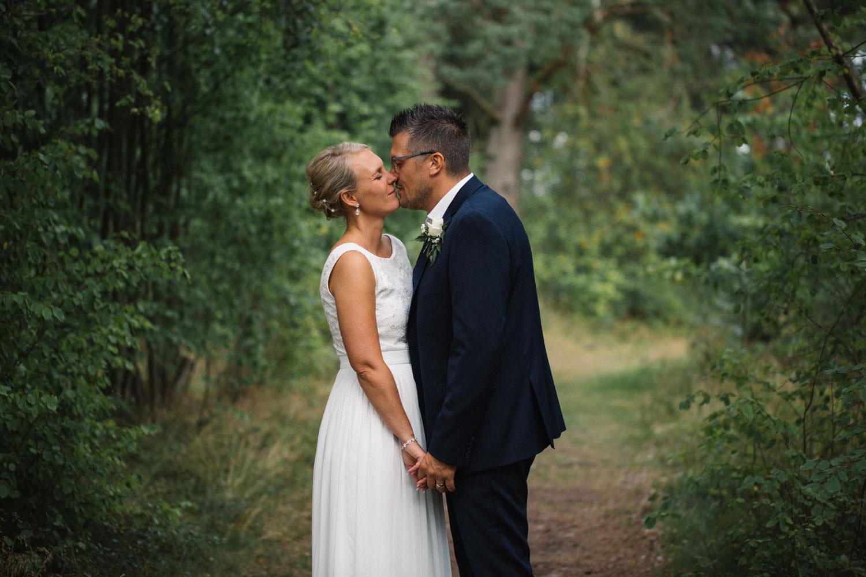 Rofyllt bröllopsporträtt på brudpar i skogen. Fotograf är Tove Lundquist. Brudklänning kommer från Sofia Moore. Kostym från Dressmann.