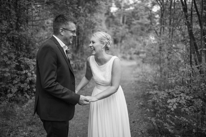 Svartvitt bröllopsporträtt på skrattande brudpar vid Oknö. Brudklänning kommer från Sofia Moore. Kostym från Dressmann.