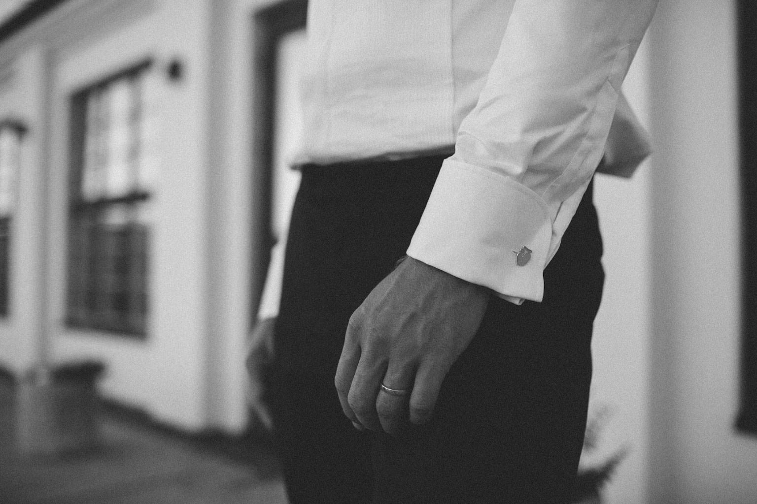Detalj på manschettknapp på brudgum. Plats är Norrgavelhuset, Kafferosteriet på Österlen. Kläder är från Oscar Jacobsson. Foto: Tove Lundquist, verksam bröllopsfotograf i Skåne.