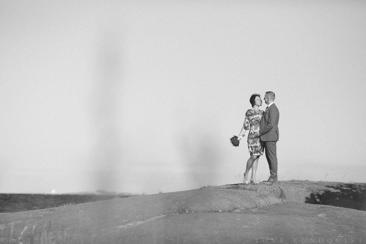Svartvitt foto på brudpar som står på klipporna vid Ernemar Småbåtshamn, Oskarshamn.