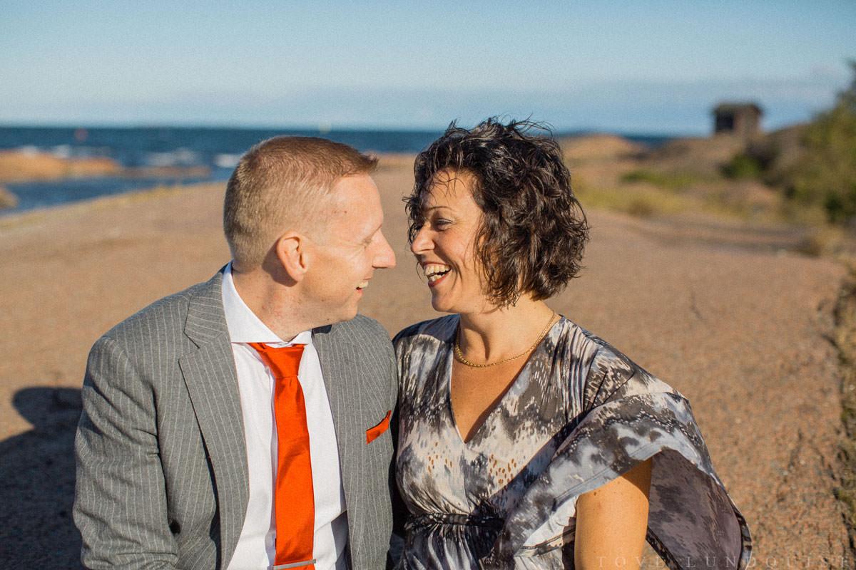 Bröllopsporträtt i färg på skrattande par.