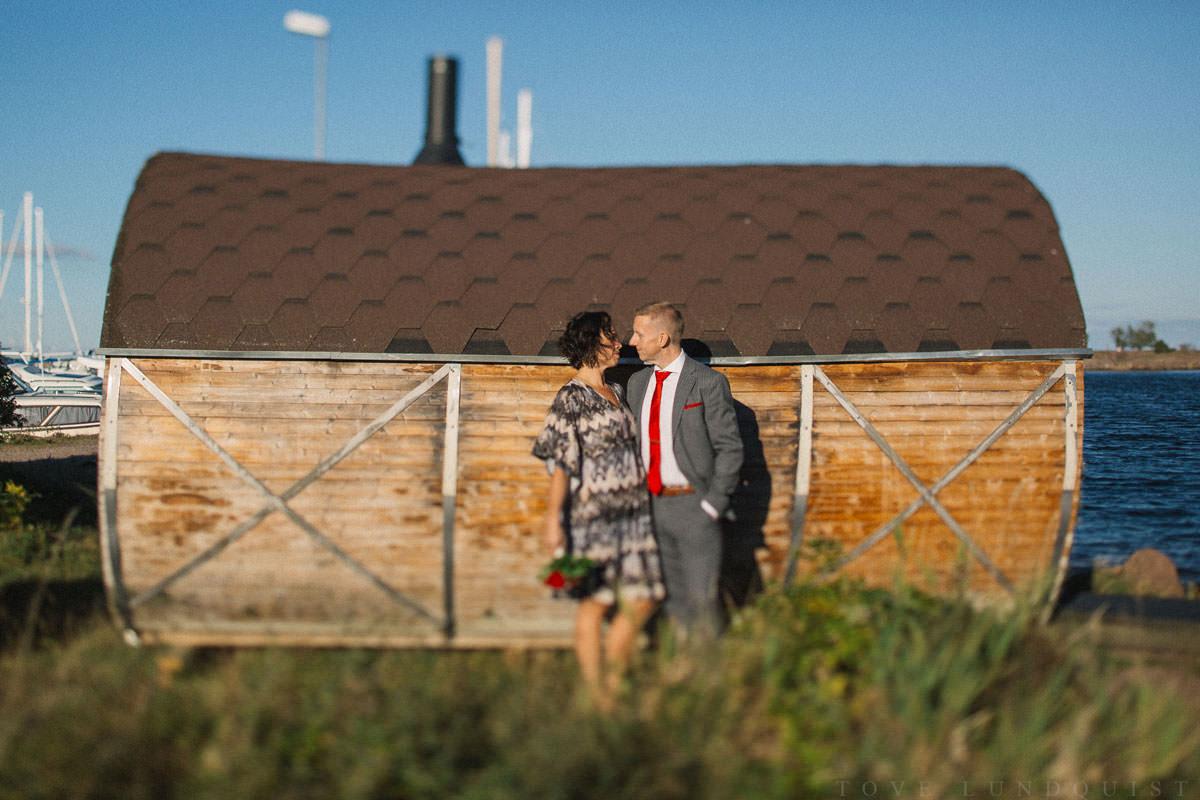 Bröllopsporträtt i färg, tagen vid bastu i trä, Ernemar Småbåtshamn i Oskarshamn. Tilt-Shift.