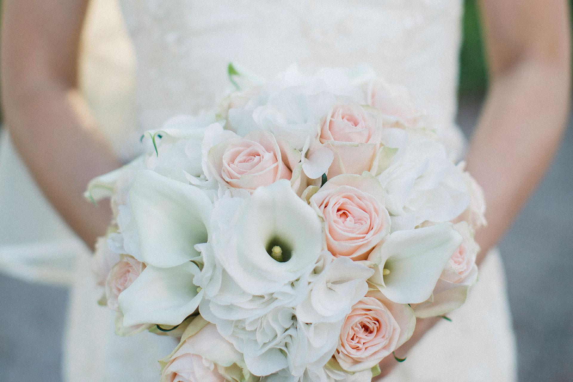 Vacker brudbukett med rosa rosor och vit kalla. Bröllopsfotograf Tove Lundquist har tagit bilden. Florist: Trolldruvans blomsterhandel.