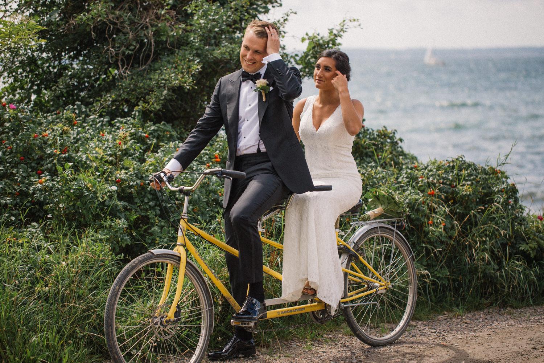 Internationellt svenskt-amerikanskt bröllop på Ven, brud och brudgum på gul tandemcykel. Foto: Tove Lundquist.