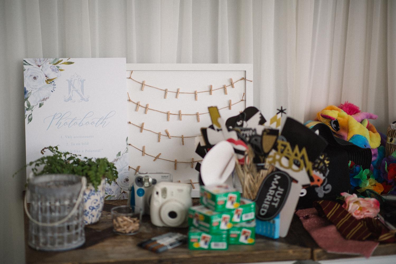 Foto i färg på Photo Booth attiraljer under ett strandbröllop på Ystad Saltsjöbad, Skåne. Unica Forma har designat och tryckt skylten.