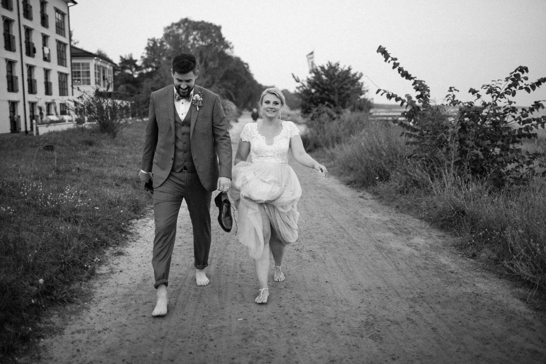 Golden hour porträtt på brudpar under ett strandbröllop på Ystad Saltsjöbad i Skåne, brudparet var barfota. Brudklänning från bohemiska Abby Waits. Brudgummens kläder är Corneliani från Olséns Mode. Foto: Tove Lundquist.
