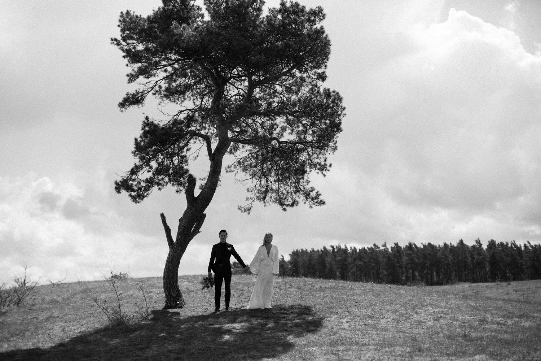 Svartvitt fotografi på brudpar under det ensamma trädet i Haväng där deras utomhusvigsel skedde. Paret hade planerat ett elopement bröllop i Skåne. Bröllopskläder: Tiger of Sweden samt Asos. Bröllopsfotograf är Tove Lundquist.