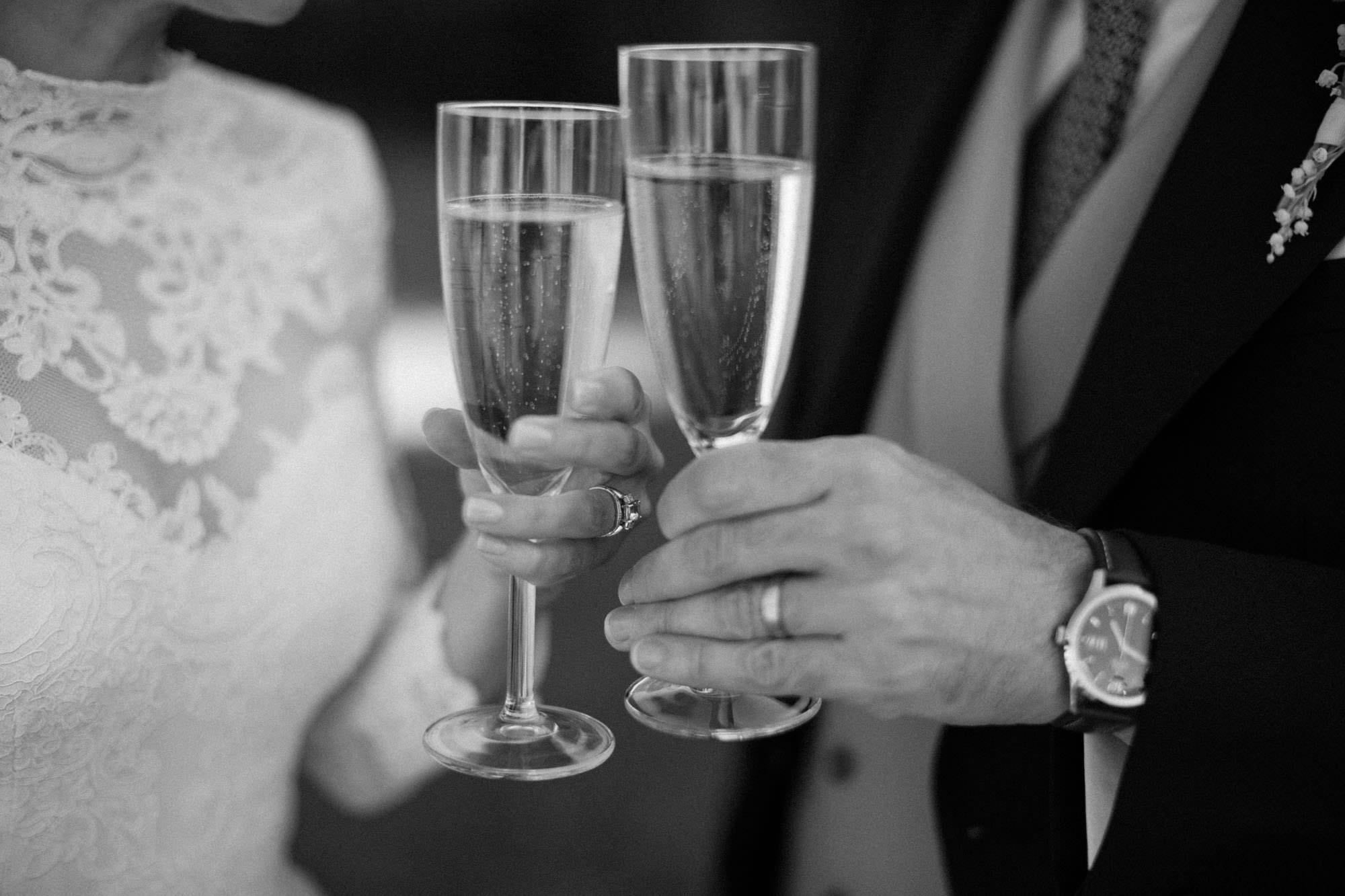 Svartvitt foto på brudpar som skålar. Brudklänningen heter Eternity Dress och är från Ida Sjöstedt Couture. Bröllopsfotograf är Tove Lundquist, bröllopslokalen är Idala Gård i Skåne.